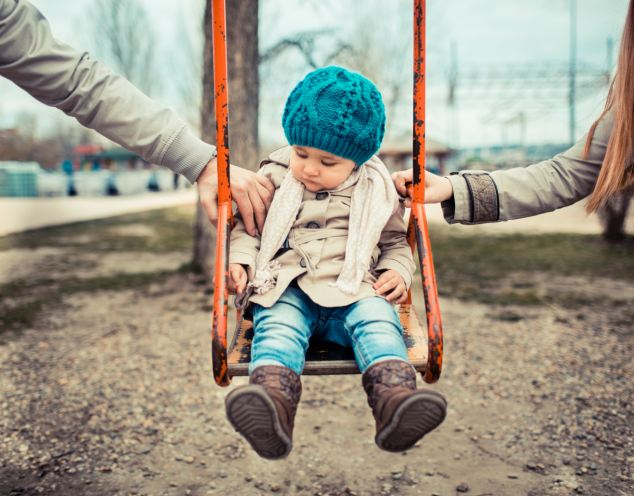 Sad child on a swing, in-between her  divorced parents holding her separately.; Shutterstock ID 132049541